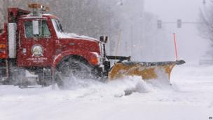 A city snow plough clears a street in an almost deserted Springfield, Illinois, as strong winds and snow move through the Midwest