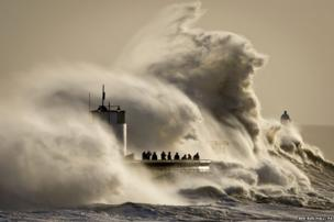 People watch and photograph enormous waves as they break on Porthcawl harbour, South Wales