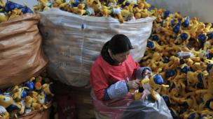 At a factory in Tianchang, China, a woman makes Fuleco the Armadillo, a soft toy of the official mascot of the 2014 World Cup football tournament