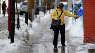 Woman walks on ice-covered pavement in Ottawa Ontario, Canada (6 Jan 2014)