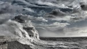 A towering wave hits Porthcawl's lighthouse