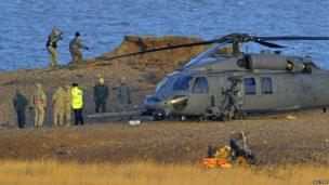 A Pave Hawk helicopter, military personnel and emergency services attend the scene of a helicopter crash on the coast near the village of Cley in Norfolk