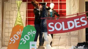 A clothing store employee prepares her store window with discount signs in Paris