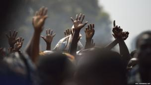 Displaced people raise their hands as they wait for food distribution, near Mpoko, Bangui's airport