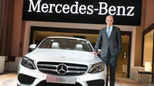 Dieter Zetsche, Chairman of the Board at Mercedes-Benz, poses next to a 2015 C-Class before the start of a media event at the North American International Auto Show
