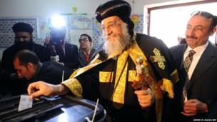 Pope Tawadros II, head of the Egyptian Coptic Orthodox Church, casts his vote on a new constitution at a polling station in Cairo on 14 January 2014