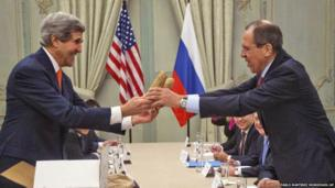 US Secretary of State John Kerry, left, gives a pair of Idaho potatoes as a gift to Russia's Foreign Minister Sergey Lavrov at the start of their meeting in Paris on 13 January 2014