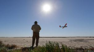 External pilot Michael Caciennne controls a drone over mud flats at a ranch near Sarita, Texas