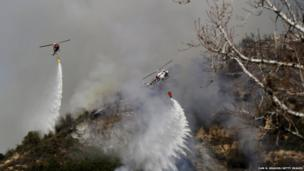 Helicopters work to control wildfires as they burn through hillsides in Azusa, California