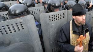 An Orthodox priest holds a cross in front of riot policemen in Kiev