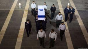 Israeli honour guards carry the coffin of former prime minister Ariel Sharon in to the Knesset
