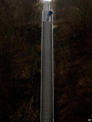 "A man rests on the so called ""stairway to heaven"" which climbs up to the top of a former coal miners dump in Neukirchen-Vluyn, western Germany, on Monday Jan.20,2014. The stairway has 352 steps and takes the altitude of 54 meter (162ft), often used for sports activities."