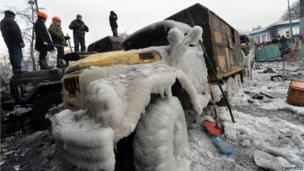 People stand on a barricade during protests in Kiev on 21 January 2014.