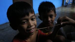 Children playing with spiders an evacuation centre.