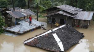 A resident stands on the roof of his home that is submerged in flood water.