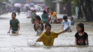 Residents in the Philippines wade through a flooded road to reach higher ground to try to escape flood waters.