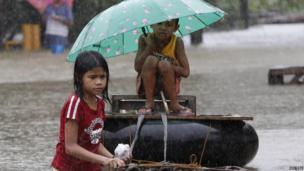 A girl pulls her brother on a makeshift raft along a flooded portion of a road in Butuan City.