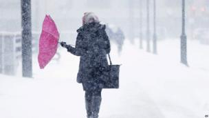 A pedestrian's umbrella is turned inside out during a winter snowstorm