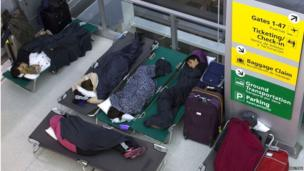 Family sleeping on camping beds in an airport lounge
