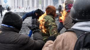 The jacket of a protester burns during clashes in the centre of Kiev