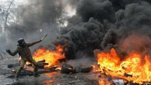 A demonstrator throws a stone as protestors clash with police in the centre of Kiev on Wednesday