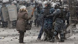 A woman holds a wooden cross in front of riot policemen during clashes with pro-European protesters in Kiev on Wednesday