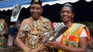 Ezekiel Cofie holds the Queen's Baton with his daughter Zetta Cofie, in Accra, Ghana.