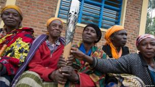 Community elders in Musanze, Rwanda hold the Queen's baton during the tour of the country.