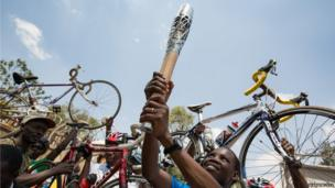 Cyclists hold the Queen's baton during the cycle to the Uganda National Olympic Committee compound in Kampala, Uganda.