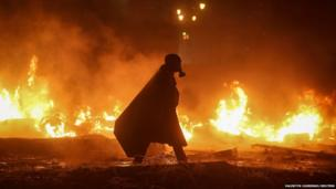 A protester walks among burning tyres at the site of clashes with riot police in Kiev