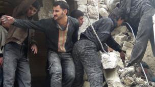 Syrians search through the rubble following a reported government airstrike on the northern city of Aleppo