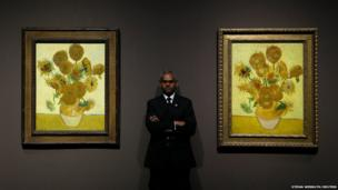A gallery supervisor poses for a photograph between Vincent van Gogh's Sunflowers,1888 (left) and Sunflowers, 1889 at the National Gallery in London