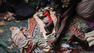 A baby sleeps on the floor of a church in Malakal