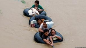 Flood victims are pulled on inflatable tyre tubes as they are evacuated from heavy flooding i nMindanao