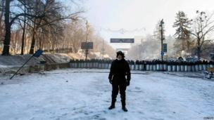 Police officer in front of row of riot police with shields, Kiev