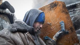 Protester takes cover behind makeshift shield, Kiev (25 Jan)