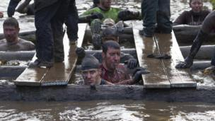 Tough Guy competitors in muddy water