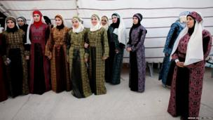 Palestinian brides wait at the backstage of a mass wedding ceremony in the West Bank city of Jericho