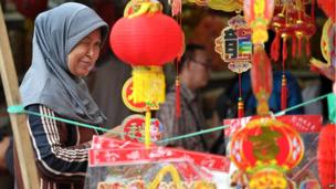 A woman stands near a stall selling Chinese new year decorations in Jakarta, Indonesia, where celebrating the Lunar New Year was banned during the three-decade reign of dictator Suharto, until his downfall in 1998