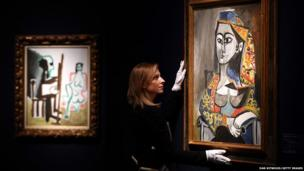 A Christie's employee poses besides Femme au costume turc dans un fauteuil by Pablo Picasso in London