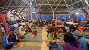 Villagers have dinner at a temporary shelter in Karo on 2 February 2014 as they left their homes following Sinabung eruptions