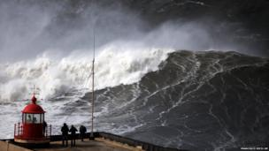 People watch huge waves approaching Nazare lighthouse on the coast of Portugal