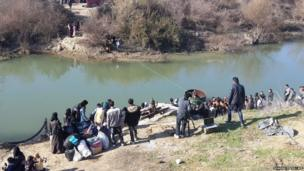 Displaced Syrians wait to cross the Orontes river into Turkey