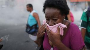 A woman covers her face to protect herself against tear gas