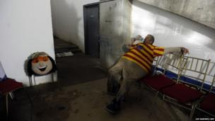 The man who works as the mascot Margarito for the 2014 Caribbean baseball series rests backstage during a game in Porlamar City, Venezuela