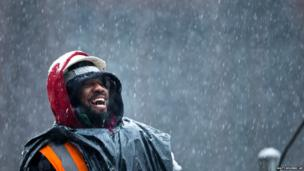A construction worker unloads a lorry during a winter snowstorm in the Brooklyn borough of New York