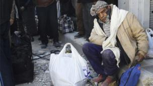 A civilian sits with his belongings as he waits to be evacuated from a besieged area of Homs 7 February 2014