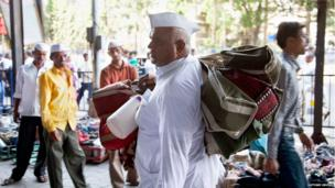 A dabbawala with several bags slung over his shoulder