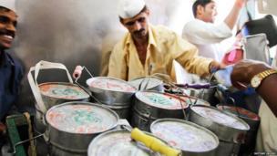 Dabbawalas, aboard a train sort their tiffin tins.