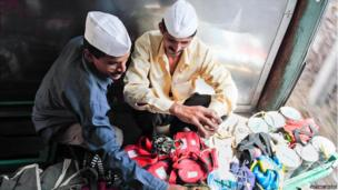 Two Dabbawalas sit on a train checking their tiffin tins.